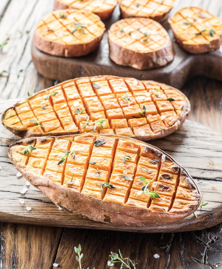 Baked batata on the old wooden table.  stock photos