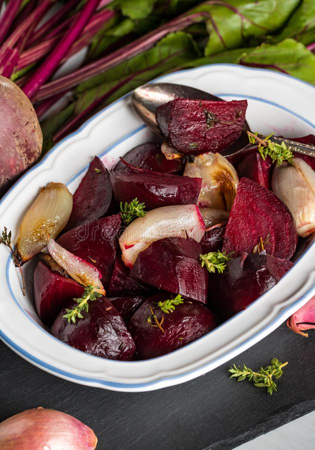 Baked beets and shallots. Close up view of a dish of baked beets and shallots garnished with thyme stock photos