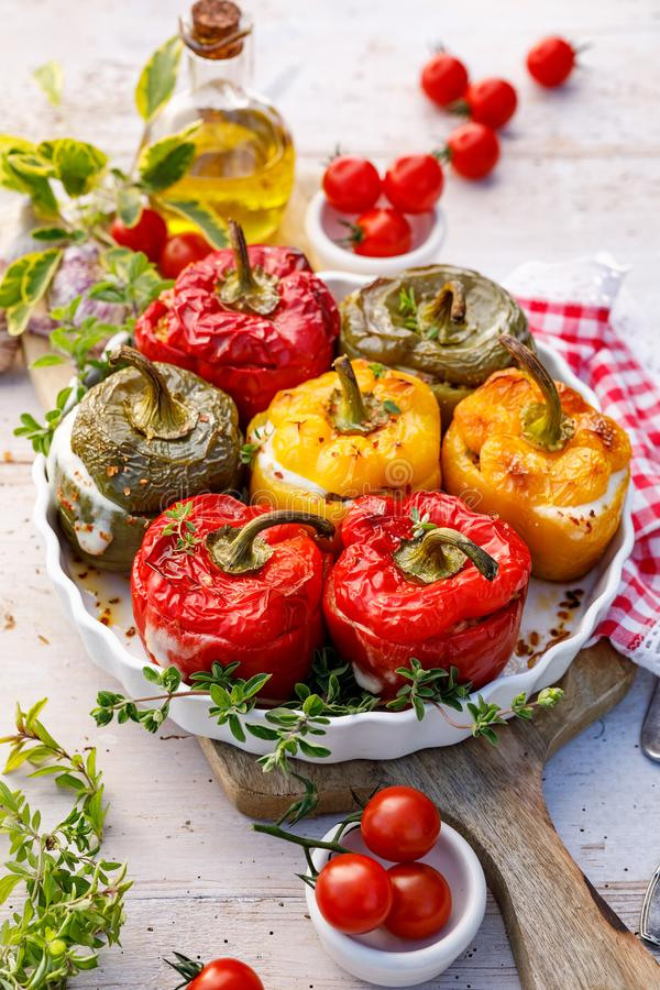 Baked bell peppers stuffed. Mushrooms, rice, cheese and herbs stuffed peppers in a baking dish on a white wooden table. royalty free stock photo