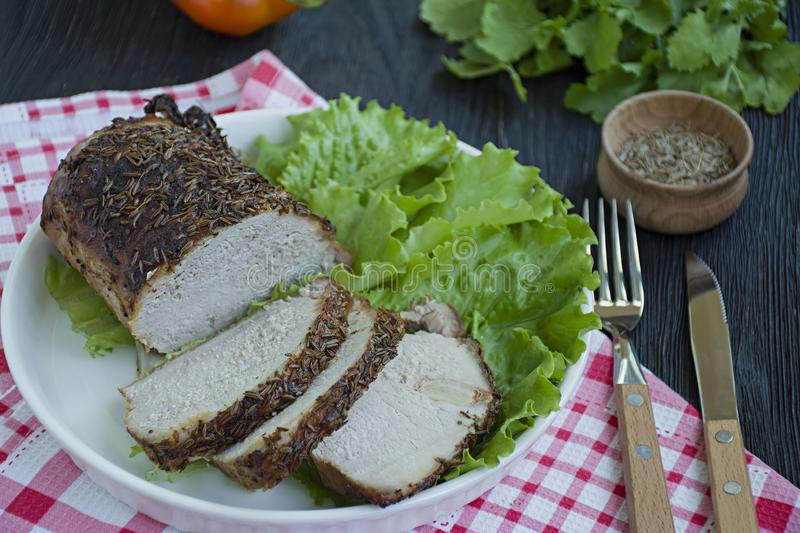 Baked boiled pork in spices sliced on a white plate with green salad. Dark wooden background royalty free stock photography