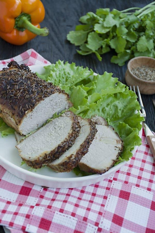 Baked a bouilli le porc en épices coupées en tranches d'un plat blanc avec de la salade verte Fond en bois fonc? photos libres de droits