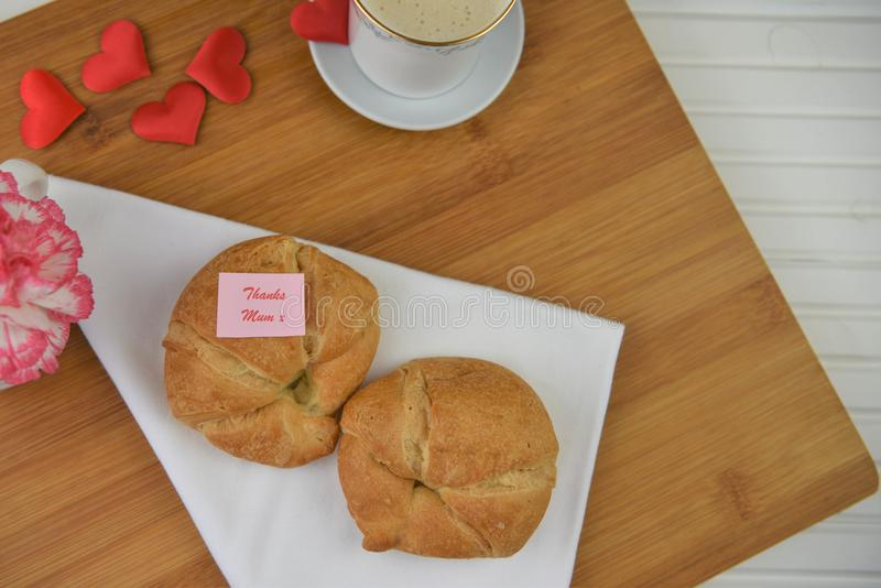 Mothers day breakfast with coffee and flowers with thanks mum note. Baked breakfast of warm croissants served on a napkin and tray. With love heart shape royalty free stock photography