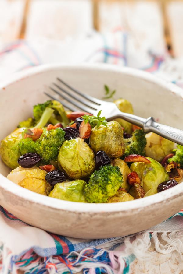 Baked Brussel sprouts. With almonds and grapes royalty free stock image