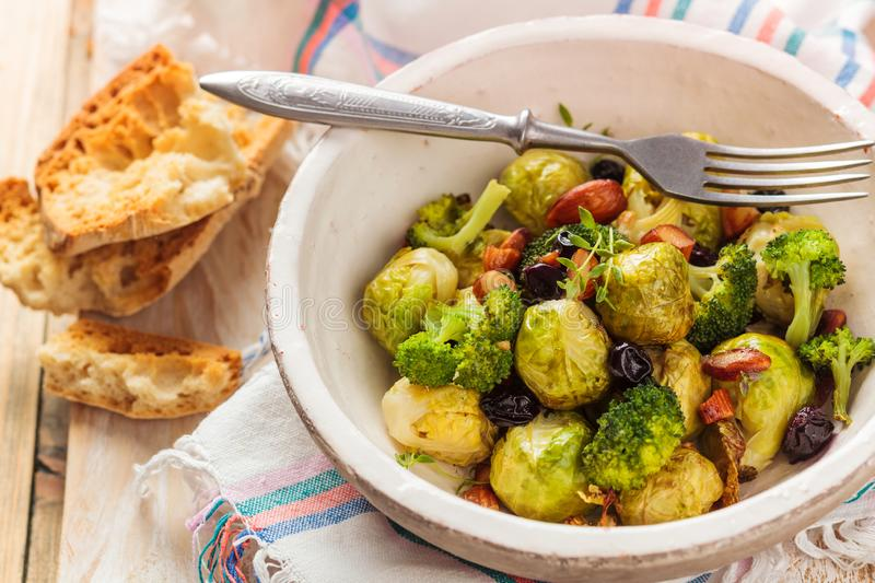 Baked Brussel sprouts. With almonds and grapes royalty free stock photography