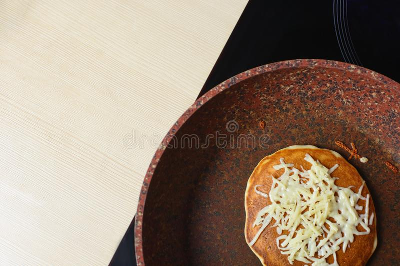 Baked without butter pancake in a pan sprinkled with grated cheese on top. Close up of tasty breakfast. Copy space stock images