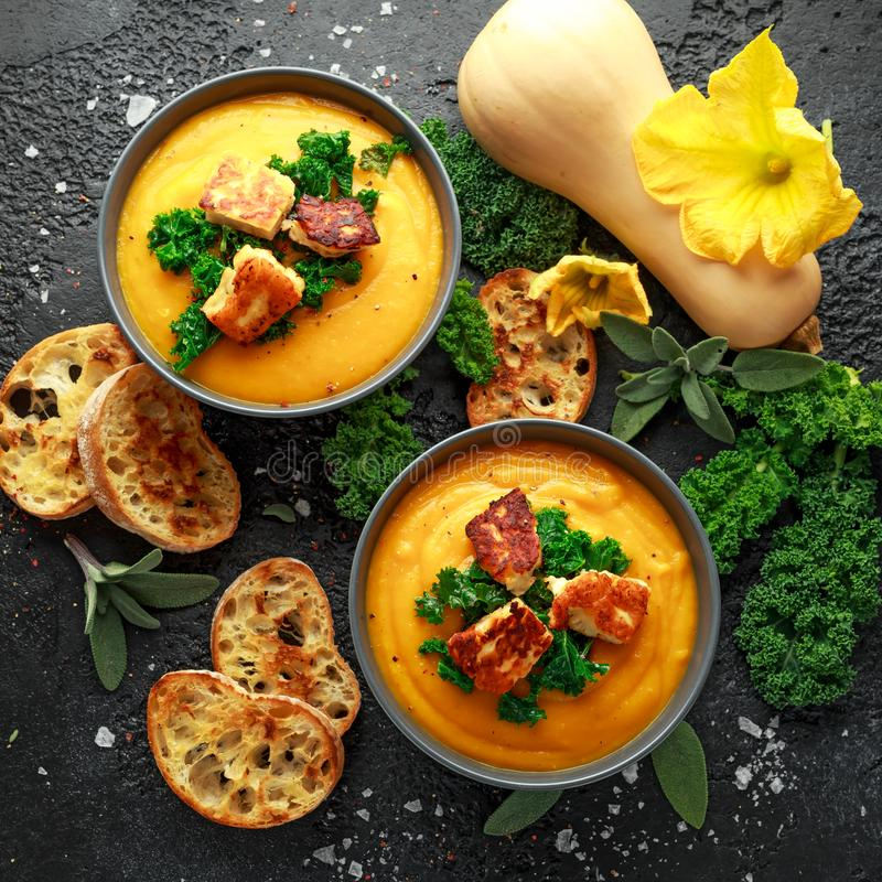 Baked butternut squash and carrot cream soup with steamed kale and fried halluomi.  royalty free stock images