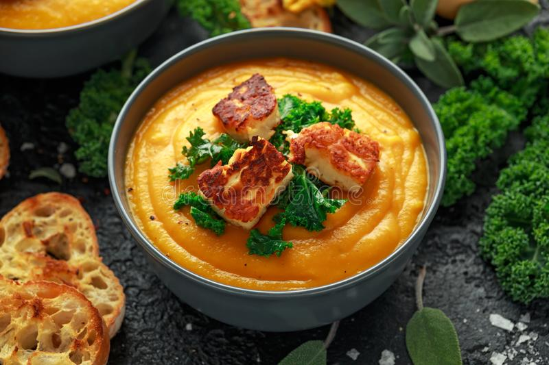 Baked butternut squash and carrot cream soup with steamed kale and fried halluomi.  royalty free stock photography