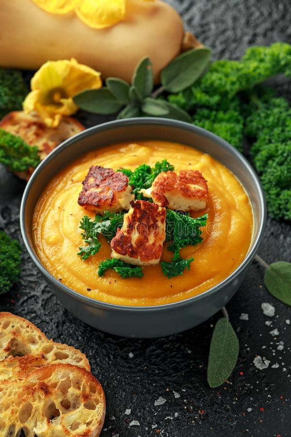 Baked butternut squash and carrot cream soup with steamed kale and fried halluomi.  royalty free stock image
