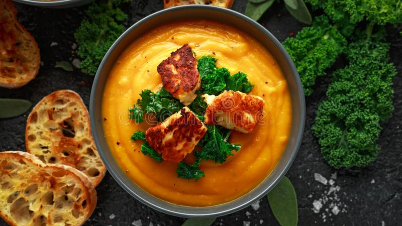 Baked butternut squash and carrot cream soup with steamed kale and fried halluomi.  stock photo