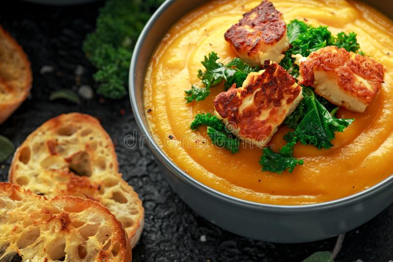 Baked butternut squash and carrot cream soup with steamed kale and fried halluomi.  stock photos