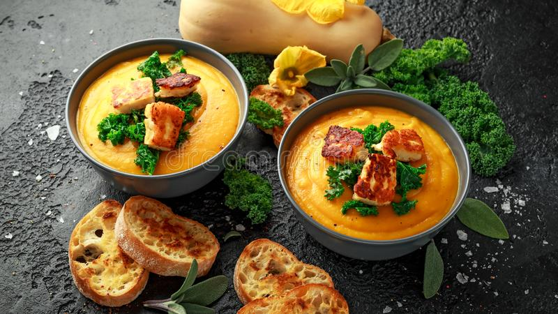 Baked butternut squash and carrot cream soup with steamed kale and fried halluomi.  royalty free stock photo