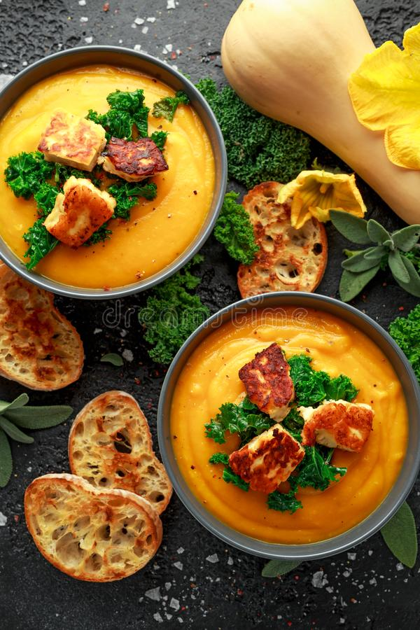 Baked butternut squash and carrot cream soup with steamed kale and fried halluomi.  stock image