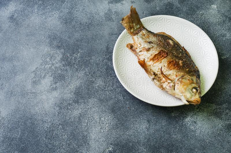 Baked carp fish on a plate. dark background. Copy space stock photo