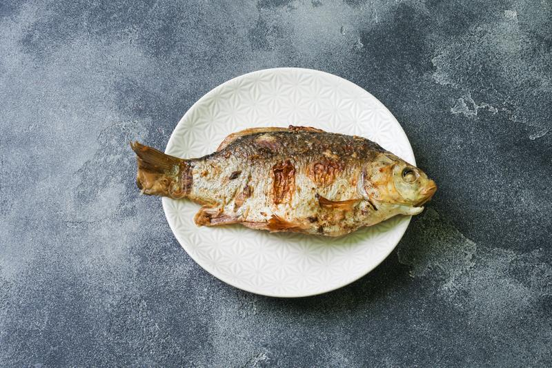 Baked carp fish on a plate. dark background. Copy space royalty free stock photo