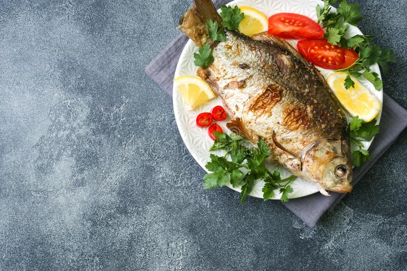 Baked carp fish with vegetables and spices on a plate on a dark table with a copy of space royalty free stock photography