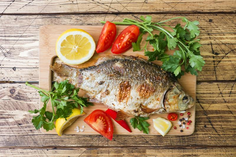 Baked carp fish with vegetables and spices on a wooden table stock images