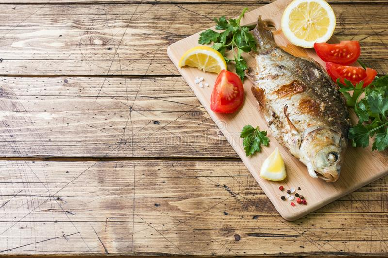 Baked carp fish with vegetables and spices on a wooden table with a copy of the space royalty free stock photography