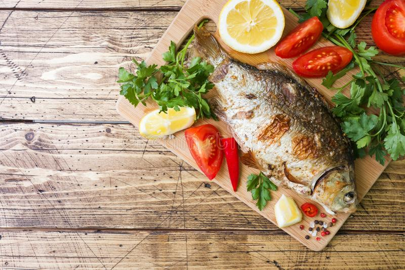Baked carp fish with vegetables and spices on a wooden table with a copy of the space stock images