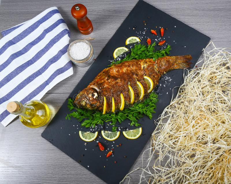 Baked carp with lime and herbs on black. top view, place for text royalty free stock images