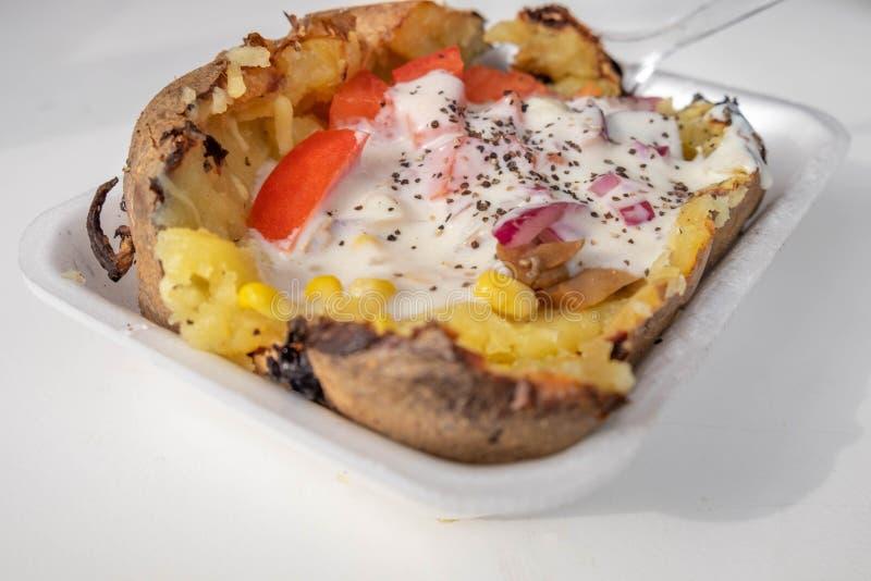 Baked carregou a batata com o queijo e creme de leite e cebolas derretidos foto de stock