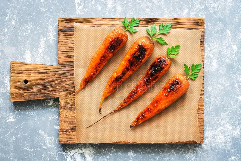 Baked carrots with green tails on a cutting board, gray background. Vegetarian food. View from above . royalty free stock photos