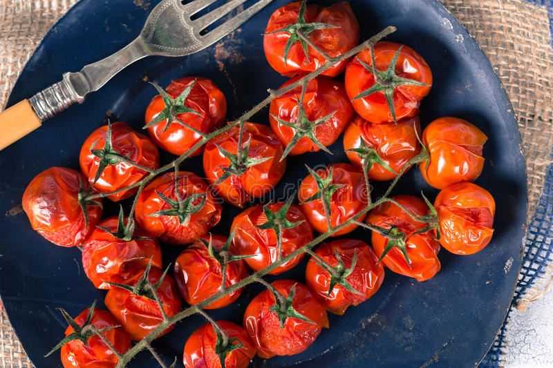 Baked cherry tomatoes. Cherry tomatoes cooked in the oven on the table royalty free stock photography