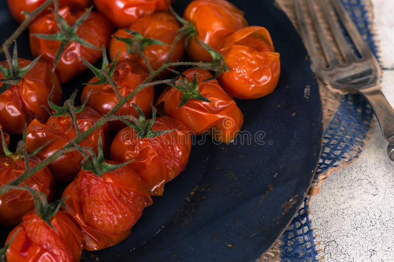 Baked cherry tomatoes. Cherry tomatoes cooked in the oven on the table stock image