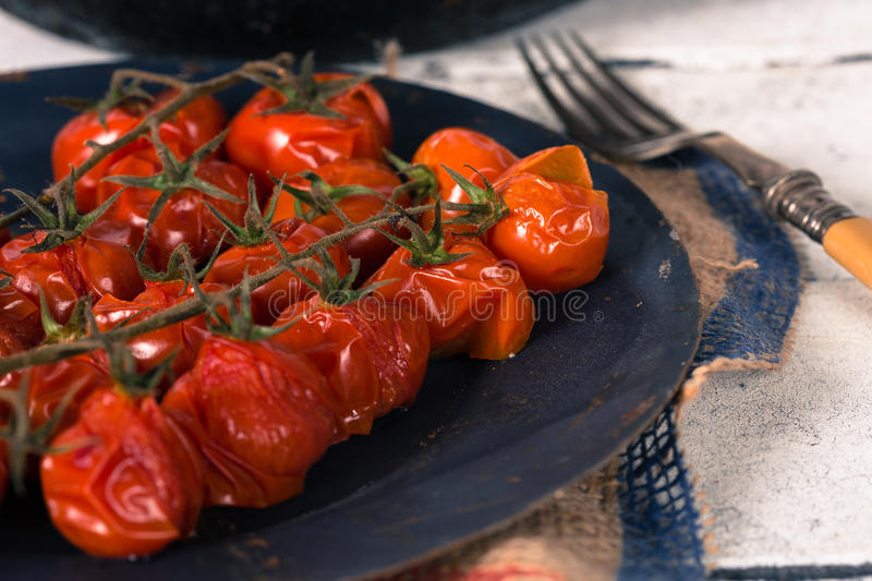 Baked cherry tomatoes. Cherry tomatoes cooked in the oven on the table stock photo