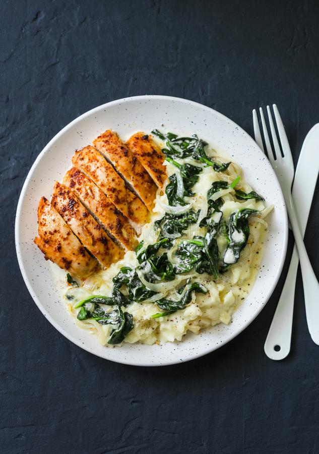 Baked chicken breast, mashed potatoes with creamy spinach on dark background, top view. Comfort food royalty free stock photo