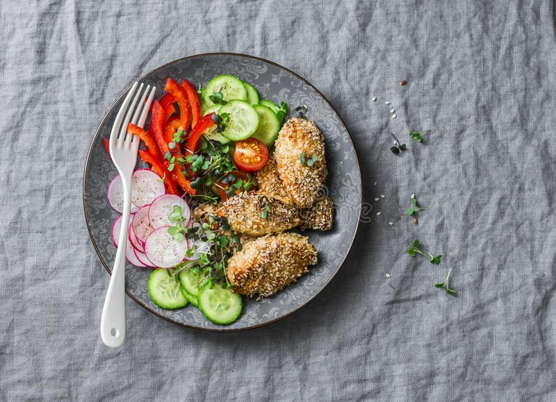 Baked chicken breast with sesame and fresh vegetables salad - healthy diet lunch on grey background stock photos