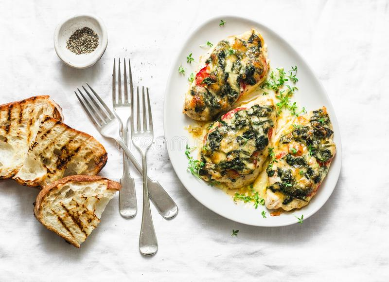 Baked chicken breast with tomatoes, spinach and mozzarella - delicious diet lunch in mediterranean style on a light background. Top view stock photo