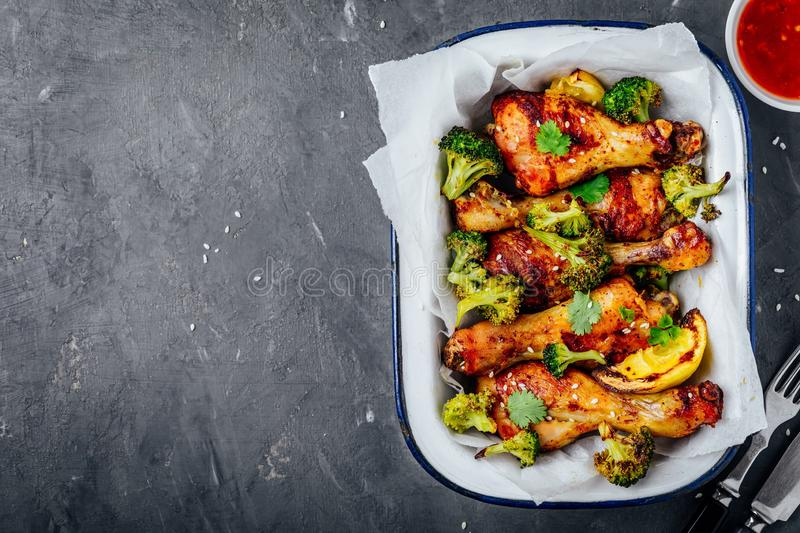 Baked chicken drumsticks with broccoli, cilantro, sesame and sweet chili sauce stock photos