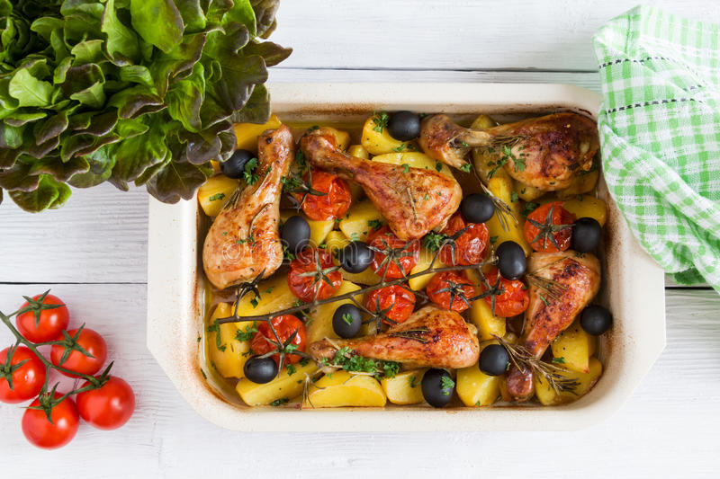 Baked chicken drumsticks in red dish. Cooked with cherry tomatoes, black olives, rosemary and potatoes. royalty free stock photos