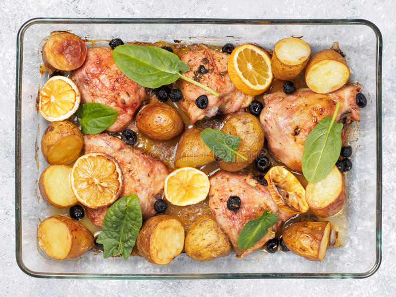 Baked chicken leg quarter with potatoes and lemon. Top view of chicken thighs with potatoes, lemon and black olives, cooked in oven on gray concrete background royalty free stock image