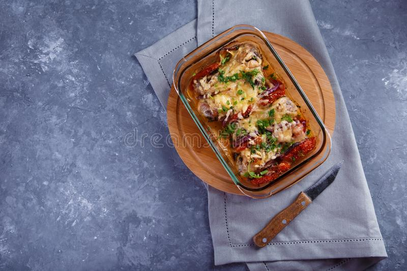 Baked chicken legs with tomatoes and onions and cheese Chicken Casserole Menu and Restaurant Concept On a gray background. Baked chicken legs with tomatoes and stock photos
