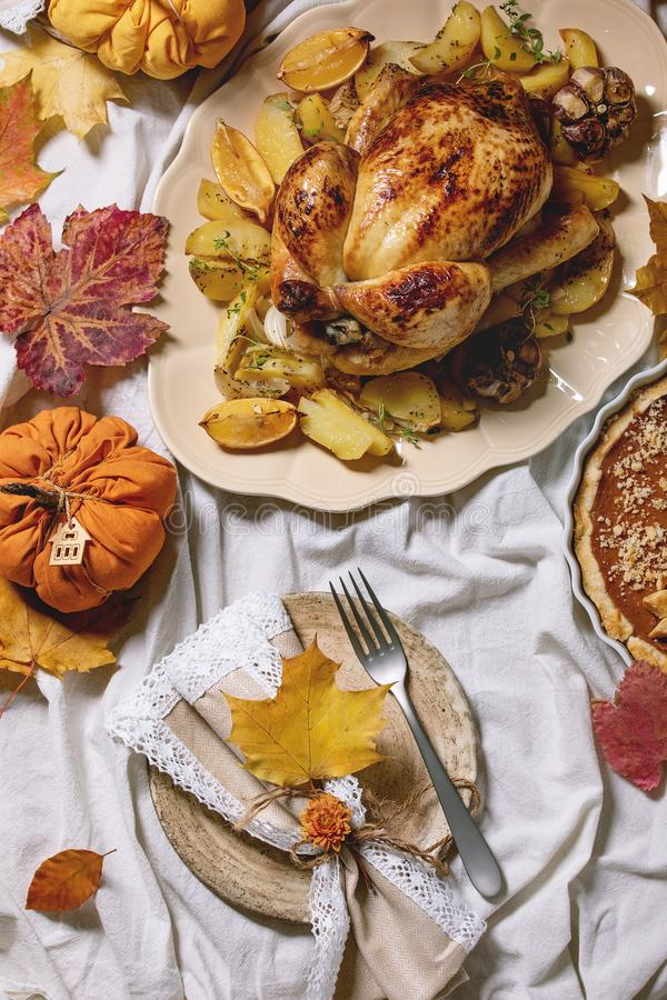 Baked chicken with potatoes. Thanksgiving or Halloween dinner with baked chicken with potatoes and lemons on big ceramic dish, pumpkin pies, plates, yellow stock photo