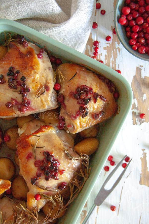 Baked chicken with red berry, rosemary and garlic. In a bowl lye on a wooden table stock photo