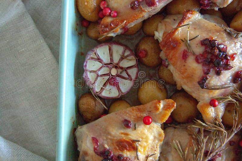 Baked chicken with red berry, rosemary and garlic. In a bowl lye on a wooden table stock photography