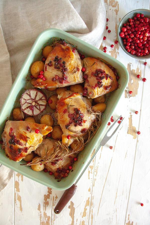 Baked chicken with red berry, rosemary and garlic. In a bowl lye on a wooden table stock images