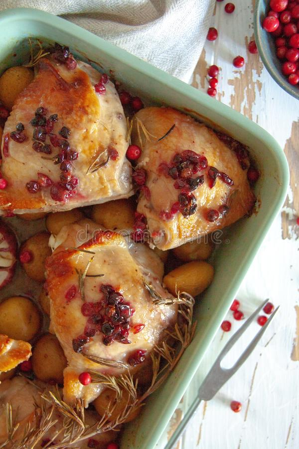Baked chicken with red berry, rosemary and garlic. In a bowl lye on a wooden table royalty free stock image