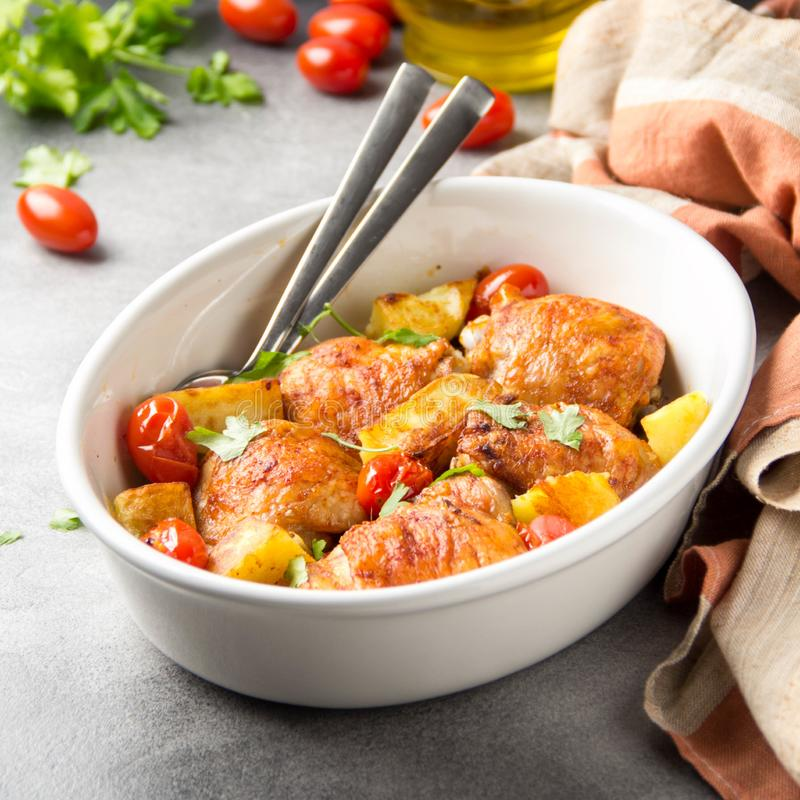 Baked chicken thighs (legs) with crispy crust, potatoes and cherry tomatoes. Simple delicious homemade dinner, traditional meal. stock photo