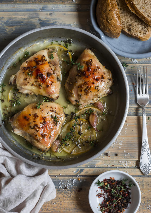 Baked chicken in white wine in the pan. On rustic wooden background. Top view royalty free stock image