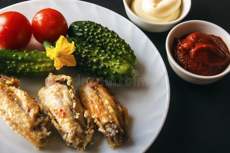 Baked chicken wings, mayonnaise, tomato paste and fresh organic vegetables on a white plate on a black background. Dietary healthy stock image
