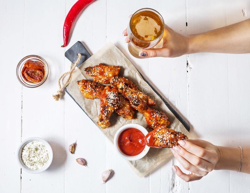Baked chicken wings with sauce on white wood background. Woman hands hold glass of beer royalty free stock image