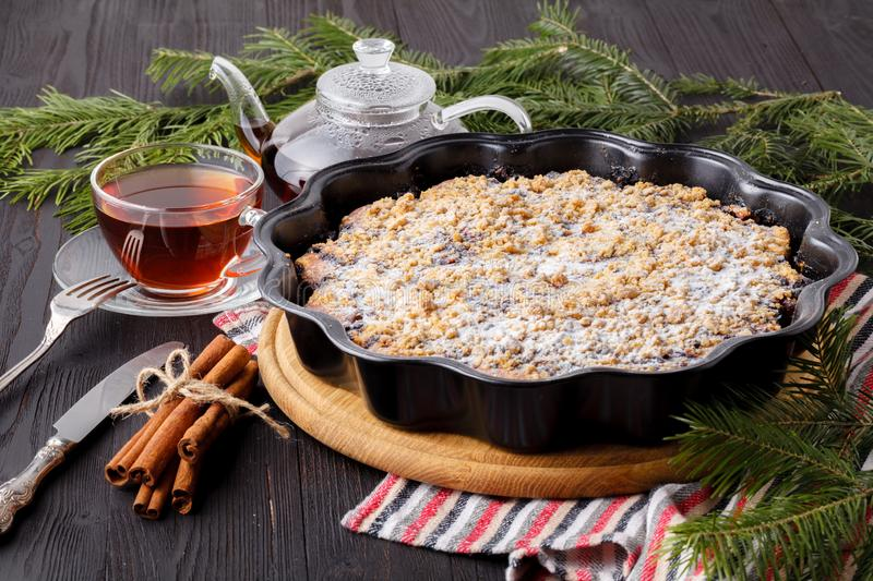 Baked Christmas cake with cinnamon, nuts and dried fruits in loaf tin on festive rustic table stock images