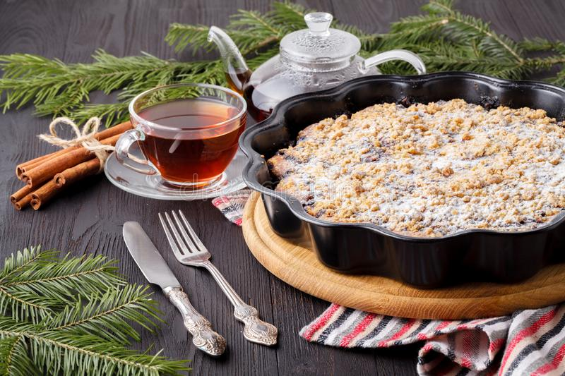 Baked Christmas cake with cinnamon, nuts and dried fruits in loaf tin on festive rustic table stock photos