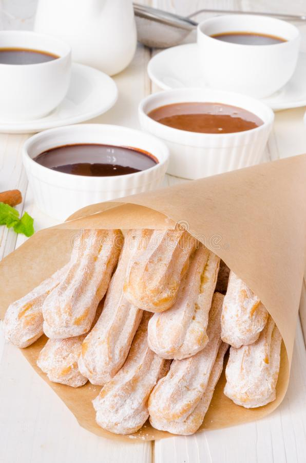 Baked churros with cinnamon, powdered sugar, chocolate and caramel sauce. Spanish cuisine royalty free stock photography