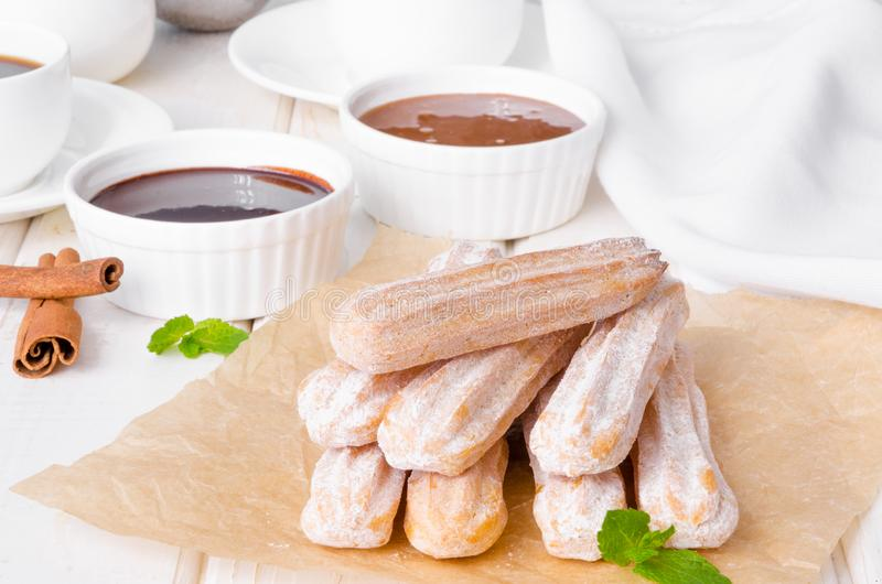 Baked churros with cinnamon, powdered sugar, chocolate and caramel sauce. Spanish cuisine stock photo