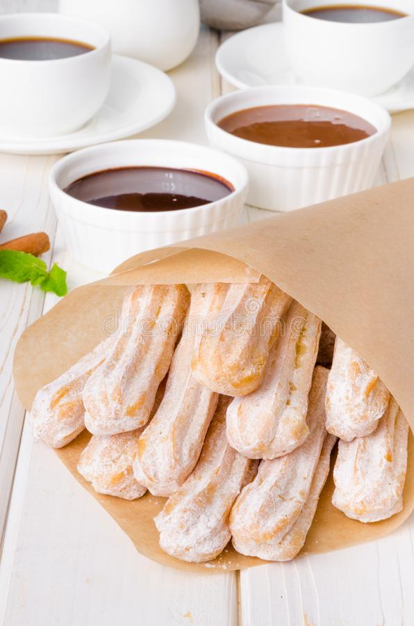 Baked churros with cinnamon, powdered sugar, chocolate and caramel sauce. Spanish cuisine royalty free stock image