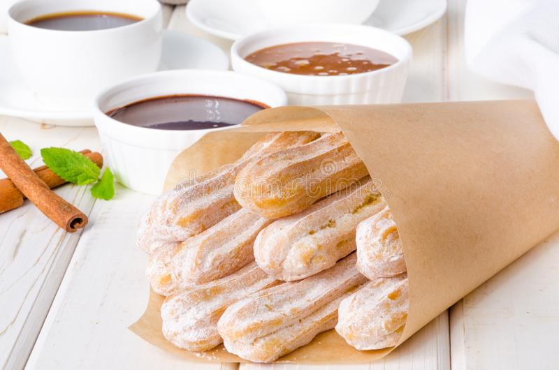 Baked churros with cinnamon, powdered sugar, chocolate and caramel sauce. Spanish cuisine stock image